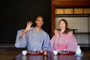 浴衣姿で手を振る外国人カップルの写真素材 [FYI02058899]