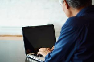 ノートパソコンを操作するシニア男性の写真素材 [FYI02058914]