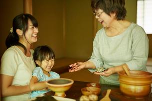 おにぎりを作る三世代女性ファミリーの写真素材 [FYI02058922]