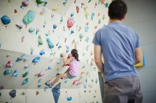 ボルダリングをする女の子と見守る父親の写真素材 [FYI02058930]