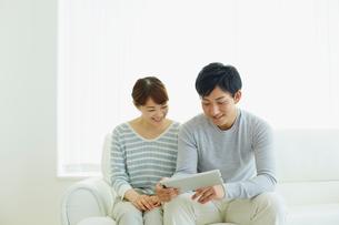 タブレットPCを見る若いカップルの写真素材 [FYI02058960]