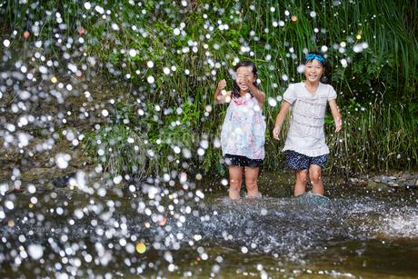 川遊びをする女の子2人と水しぶきの写真素材 [FYI02058989]