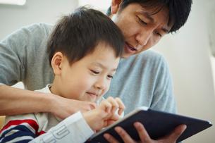 タブレットPCを見る父親と男の子の写真素材 [FYI02058994]