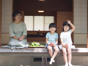 縁側に座る祖母と女の子2人の写真素材 [FYI02059009]