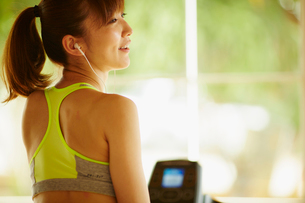 イヤホンをつけたスポーツウェア姿の女性の写真素材 [FYI02059010]