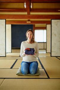 風呂敷包みを持って正座する外国人女性の写真素材 [FYI02059011]