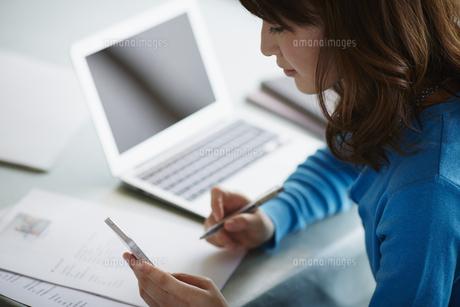 ノートパソコンやスマートフォンで仕事をする女性の写真素材 [FYI02059063]