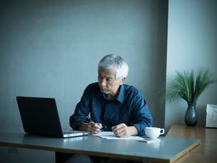 ホームオフィスで仕事をするシニア男性の写真素材 [FYI02059073]