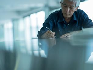 書類を書くシニア男性の写真素材 [FYI02059104]