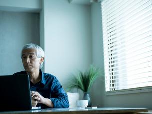 ホームオフィスで仕事をするシニア男性の写真素材 [FYI02059113]