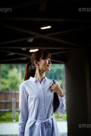 バッグを持ちエントランスを歩く女性の写真素材 [FYI02059140]