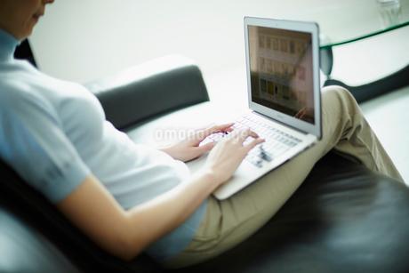 ソファに座りノートパソコンを操作する女性の写真素材 [FYI02059145]