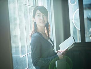 本を持ち窓の外を見る女性の写真素材 [FYI02059171]