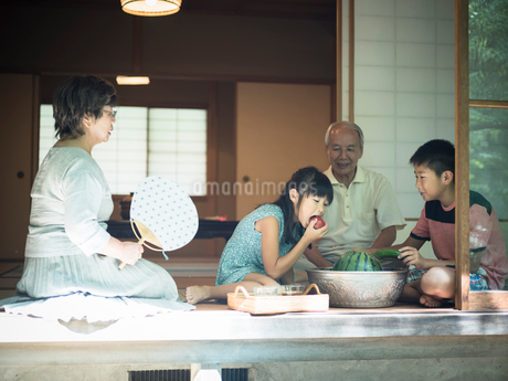 縁側で冷えた野菜を食べる孫たちと祖父母の写真素材 [FYI02059191]