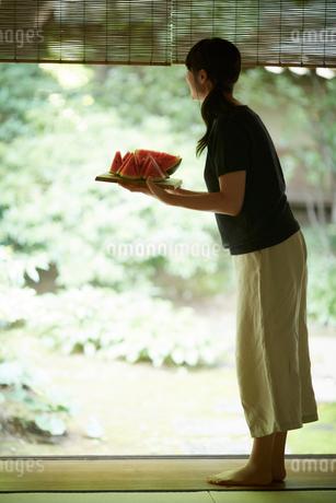 スイカを持って庭を眺める女性の写真素材 [FYI02059201]