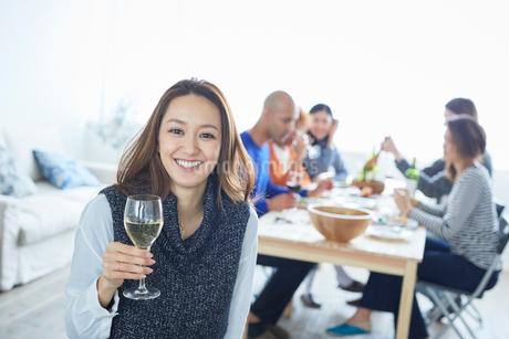 白ワインを持つ日本人女性と食事をする仲間たちの写真素材 [FYI02059223]