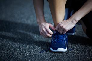 ランニングシューズを履く女性の手と足の写真素材 [FYI02059241]