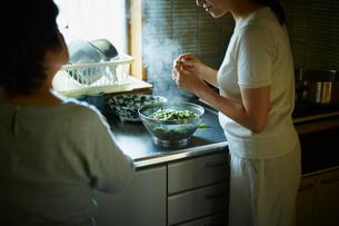 枝豆の茹で具合を確認する娘と母親の写真素材 [FYI02059254]