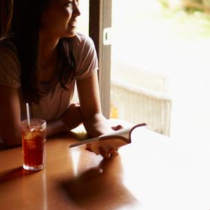 本を持ち窓の外を眺める女性の写真素材 [FYI02059262]