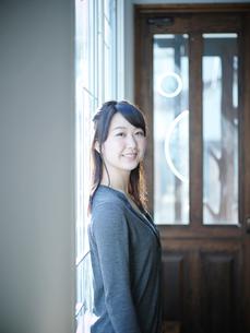 窓辺に立つ笑顔の女性の写真素材 [FYI02059279]