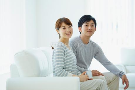 ソファに座る若いカップルの写真素材 [FYI02059361]