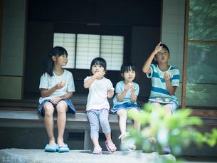 縁側でおにぎりを食べる子供たちの写真素材 [FYI02059400]