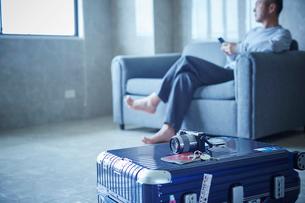 スーツケースとソファに座るミドル男性の写真素材 [FYI02059424]