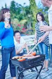 ガーデンパーティーでバーベキューをする2組の夫婦の写真素材 [FYI02059438]