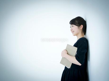 本を抱えて壁に寄りかかる女性の写真素材 [FYI02059439]