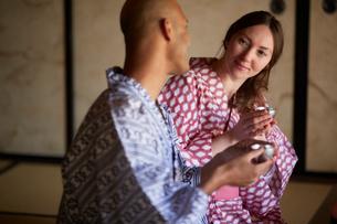 浴衣姿で日本酒を楽しむ外国人カップルの写真素材 [FYI02059447]