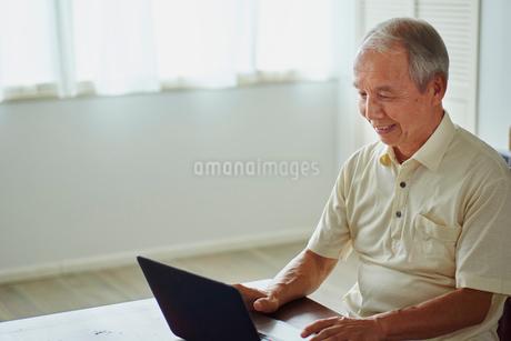 ノートパソコンを操作するシニア男性の写真素材 [FYI02059498]