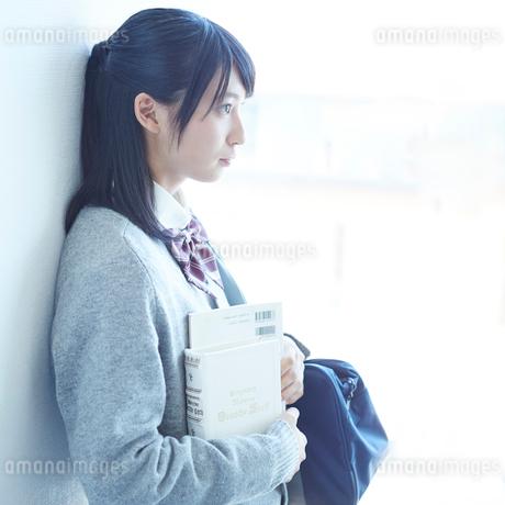 壁に寄りかかる女子学生の横顔の写真素材 [FYI02059505]