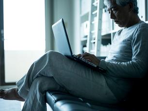 ノートパソコンを操作するシニア男性の写真素材 [FYI02059541]