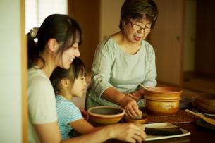 おにぎりを作る三世代女性ファミリーの写真素材 [FYI02059549]
