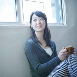 コーヒーカップを持ってくつろぐ女性の写真素材 [FYI02059572]