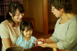 おにぎりを作る三世代女性ファミリーの写真素材 [FYI02059578]