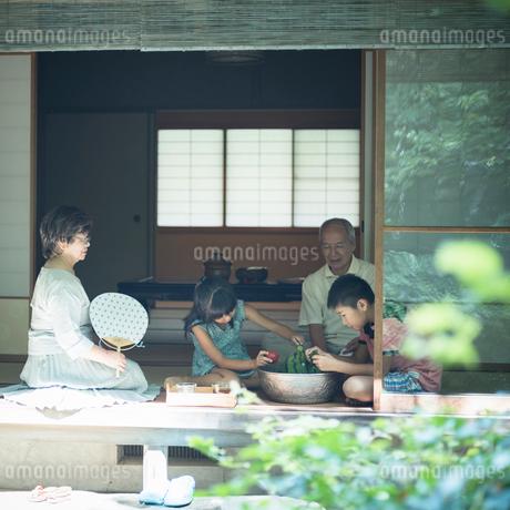 縁側でスイカや野菜を冷やす祖父母と孫たちの写真素材 [FYI02059585]