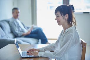 ノートパソコンを操作する女性と読書をする男性の写真素材 [FYI02059587]