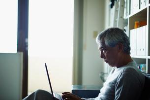 ノートパソコンを操作するシニア男性の写真素材 [FYI02059590]