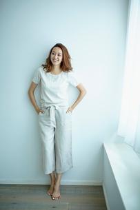 白い壁の前に立つ笑顔の女性の写真素材 [FYI02059610]