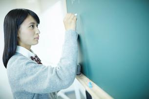 黒板に書く女子学生の写真素材 [FYI02059618]