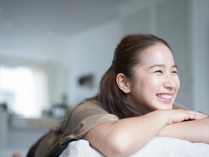 ソファの上でくつろぐ笑顔の女性の写真素材 [FYI02059619]