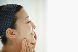 頬に触れる女性の横顔の写真素材 [FYI02059658]
