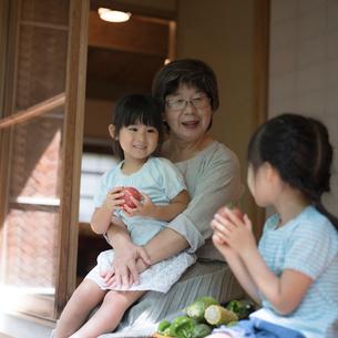 縁側に座る祖母と女の子2人の写真素材 [FYI02059702]