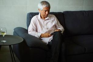 タブレットPCを操作するシニア男性の写真素材 [FYI02059708]