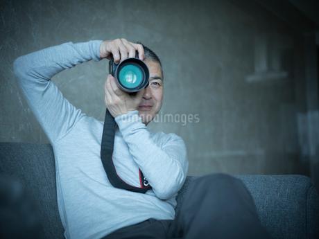 カメラを構えるミドル男性の写真素材 [FYI02059771]