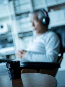 テーブルの上のコーヒーとヘッドフォンで音楽を聴くシニア男性の写真素材 [FYI02059776]