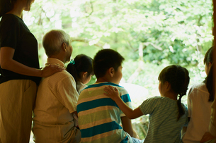 縁側で庭を眺める3世代家族の写真素材 [FYI02059783]