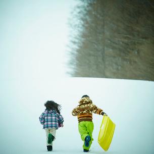 ソリを持って雪上を走る男の子と女の子の後ろ姿の写真素材 [FYI02059807]