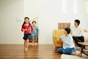 リビングルームで走り回る子供達とくつろぐ両親の写真素材 [FYI02059812]